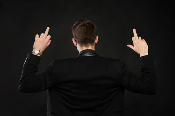 Handsome young man showing middle finger, insult sign on black background