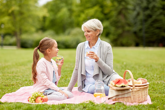 family, leisure and people concept - happy grandmother and granddaughter having picnic and drinking fruit water at summer park