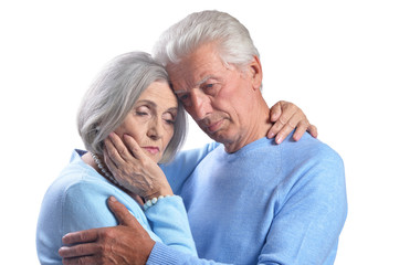 Senior couple hugging on a white background