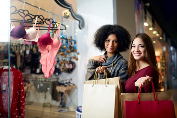 Two happy multiethnic young mixed race woman shopping for lingerie near clothing boutique shop window, decide whether to purchase. African american girl considers underwear with friend at shop front.