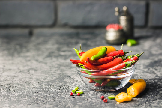 Red, yellow, green chili peppers in a bowl on dark concrete background. Selective focus, space for text.