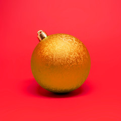 Single orange Christmas decoration ball isolated on a red background