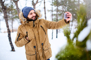 Smiling bearded man wears warm winter clothes and taking selfie photo with smartphone camera. Handsome man texting with cellphone and using apps in snowy forest. Snowfall in woods.
