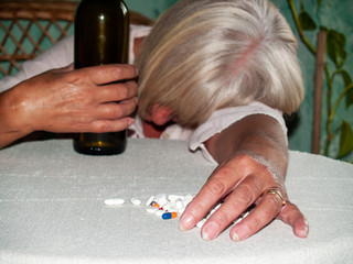 A senior woman with a bottle of wine and a large number of pills in her hand of different colors and sizes, lying on a table