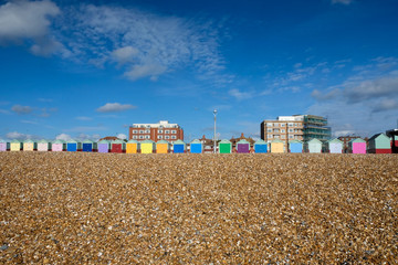 a row of Beach huts in Brighton a pebble beach is in the foreground and a big blue sky behind