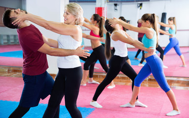Sporty mature woman with her instructor are training self-defence moves in gym.