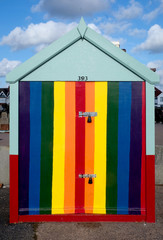 A single beach hut with a multi coloured rainbow colored door stripey yellow, pink, colours