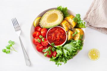 vegan buddha bowl. healthy lunch bowl with avocado, tomato, sweet corn and salsa