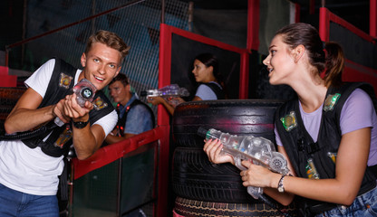 Smiling young friends playing laser tag  game with colored laser guns near tires in labyrinth