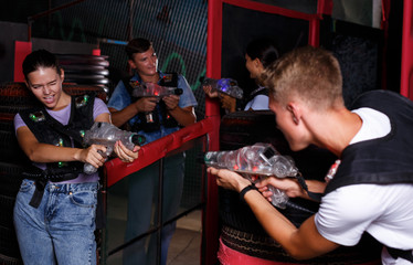 friends holding colored laser guns during laser tag game