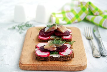 Smorrebrod, a traditional Danish open sandwich on dark rye bread with herring, pickled beets and fresh radishes.