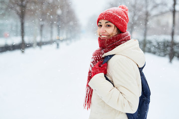 Cheerful smiling woman in white down jacket and red cap, scarf and mittens walking on the snowy street after blizzard in city. winter city after blizzards and snowfall.