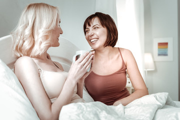 Lovingly looking. Laughing dark-haired woman spending time with her close beaming friend sitting in the bad