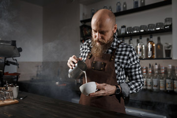 Brutal young barista in an apron makes coffee at the bar in a modern cafe