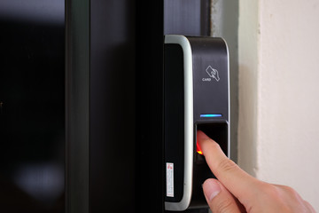 Close up of a man paste finger to biometric fingerprint scanner.