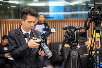Man photographer checking photo in digital camera and setting. Technological concepts.