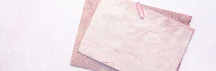 A minimalist panoramic Christmas card with snowflakes and an envelope with an old vintage paper mockup