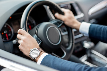 Close-up of businessman's hands on the helm of a luxury car
