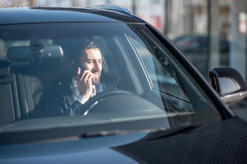 Businessman talking with phone while driving a luxury car, view from the outside through the windshield