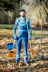 Portrait of a professional male sweeper in blue uniform with sweeping tools in the garden during the autumn time