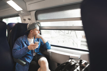 Student with a smartphone in his arms goes by train and looks in the window. Guy travels with a modern train and uses a smartphone. Using the Internet on a trip.