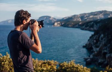 Male photographer taking photo of beautiful Italy coastline