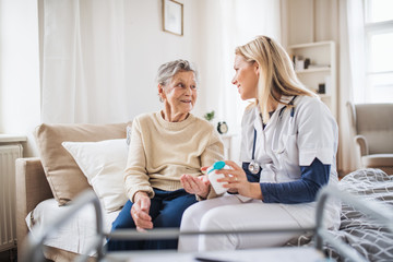 A health visitor explaining a senior woman how to take pills.