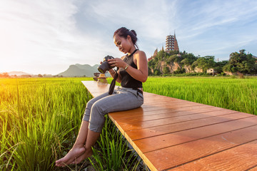 Asian woman traveler take a photo and enjoying at Wat Tham Suea background, Kanchanaburi Province, Thailand