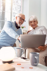 Online purchase. Aging beautiful couple smiling bright while eagerly discussing goods to be purchased online