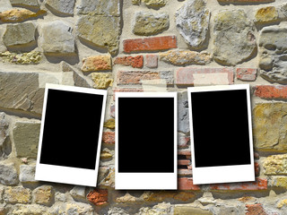 Three blank rectangular instant photo frames against ancient stone wall background