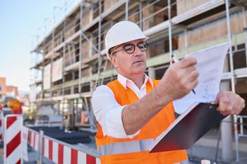 Mann, Arbeiter auf Baustelle mit Plan der Hand