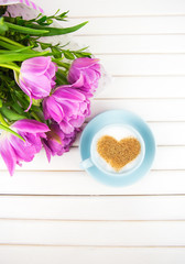 Cup of cappuccino with a heart shaped symbol and purple tulips on a wooden background.