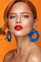 Beautiful girl with unusual accessories and make-up on a bright background. Beauty face.