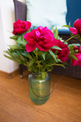 a bouquet of beautiful pions in a large vase stands on the floor near the sofa with pillows.
