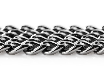 Abstract background of black decorative steel chain lying on a white background. Close-up