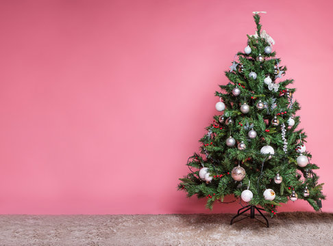 Christmas tree with beautiful ornaments on pink background