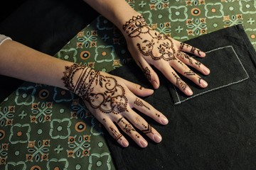 beauty concept - two hand of girl being decorated with henna mehendi Tattoo. Close-up, overhead view
