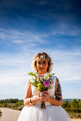 Bride poses with her bouquet under a blue sky