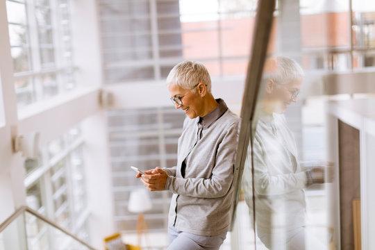 Senior businesswoman using mobile phone in modern ofice