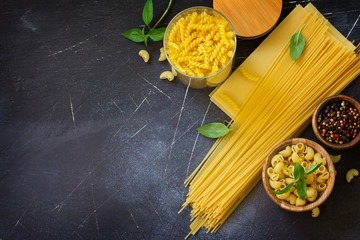 Various pasta. Ingredients for cooking pasta on a stone table. Top view flat lay background. Copy space.