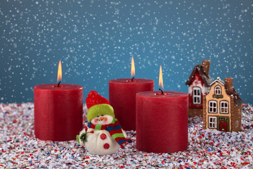 Three burning candles on the background of Christmas snowfall and toy figure snowman. Merry Christmas and happy holidays Christmas story concept.