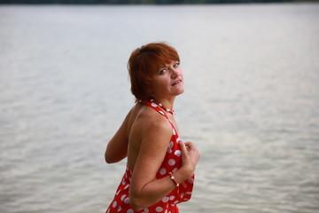 Beautiful sexy woman in red dress near the lake.
