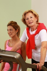 younger woman helps senior woman with Training with the treadmill