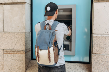 The tourist withdraws money from the ATM for further travel. Finance, credit card, withdrawal of money. Life style. Journey. Vacation. Grabs a card from the ATM.