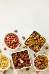Foto op Aluminium Buffet, Bar Various nuts in a ceramic bowl (walnut, almonds, pine nuts, hazelnuts) on a light stone table. The concept of a healthy dessert.Top view flat lay background. Copy space.