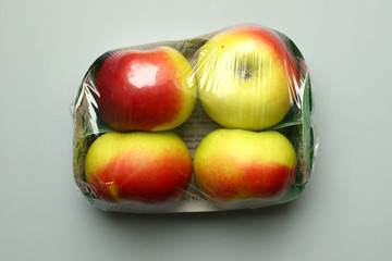 Apples, wrapped in a plastic foil as bought in a supermarket, are seen in this picture illustration