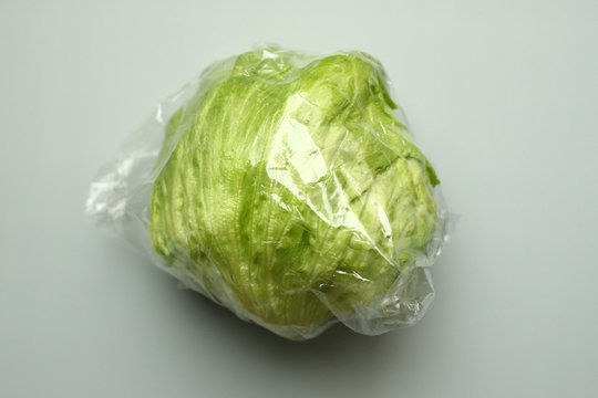 A head of lettuce, wrapped in a plastic foil as bought in a supermarket, is seen in this picture illustration