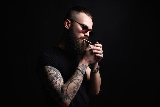 man lights a cigarette. Hipster tattoed boy