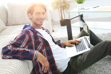 smiling young man with laptop sitting on the floor near the couch