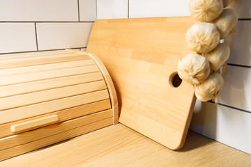 Bread bin. View of the kitchen counter with cutting Board, hanging on the wall a few heads of garlic